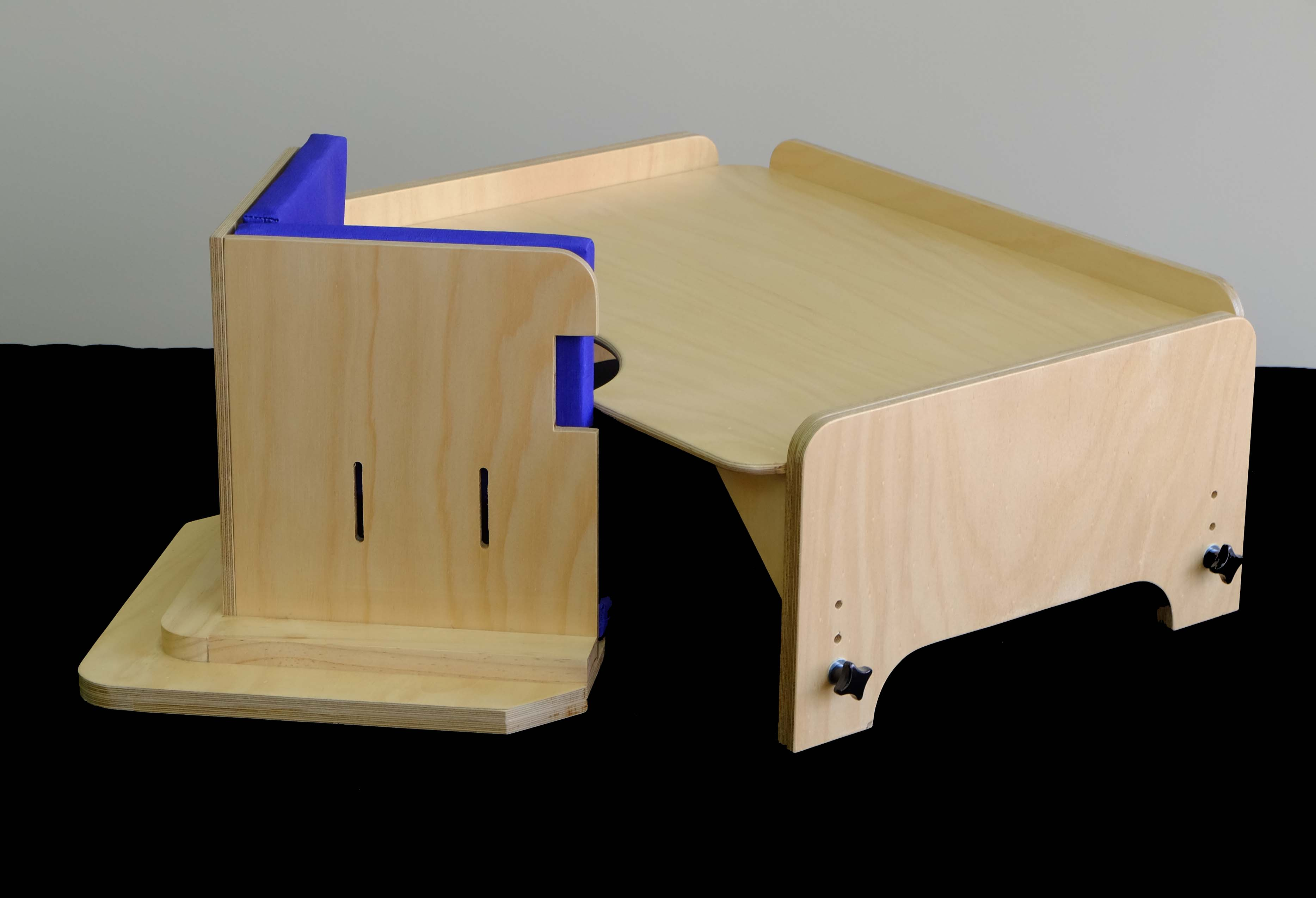 A smaller floor sitting corner chair and adjustable height table, for seating young children in a well-supported and functional position.